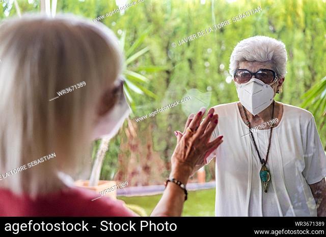 Senior woman wearing mask visiting female friend through window during curfew