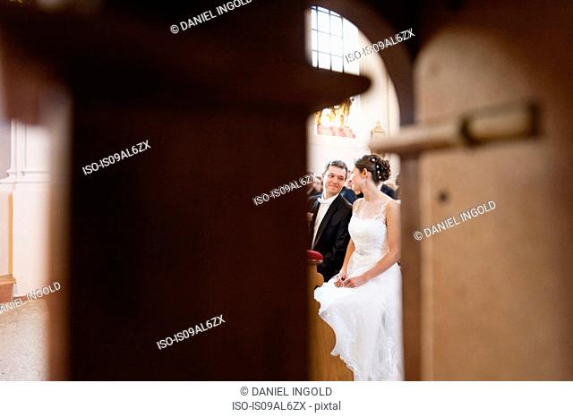 Bride and bridegroom sitting on church pew