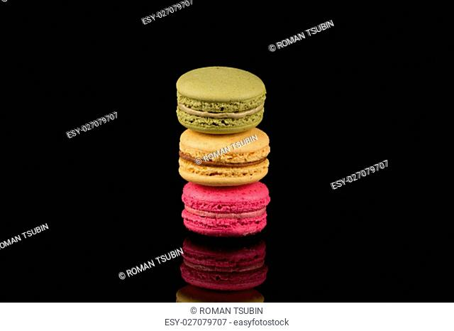 Colorful macaroons over a black background with reflection
