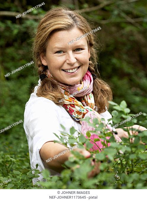 Woman picking blueberries, smiling, portrait