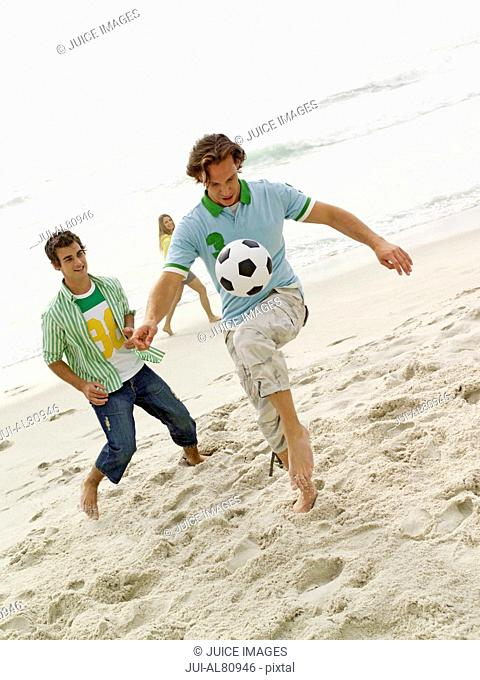 Two young men playing with soccer ball at beach
