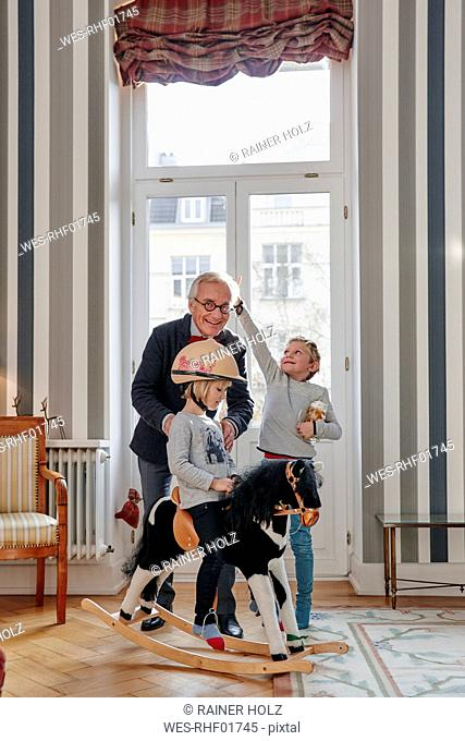 Grandfather and grandchildren playing with rocking horse