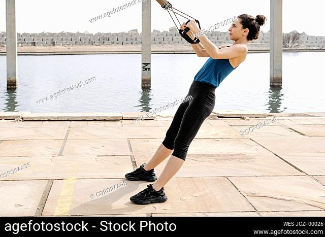 Young woman training on ropes at harbour