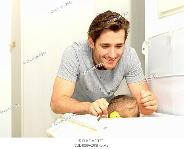 Smiling father changing baby boys nappy