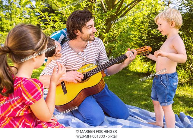 Father with children playing guitar in garden