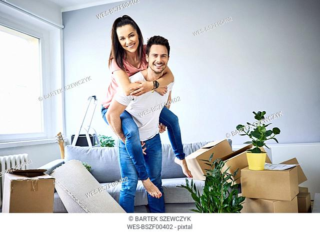 Portrait of cheerful couple moving in