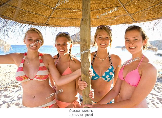 Teenage girls posing under beach umbrella