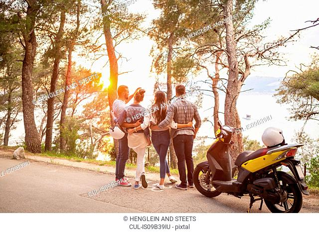 Two couples with moped looking out at sunset from coastal road, Split, Dalmatia, Croatia