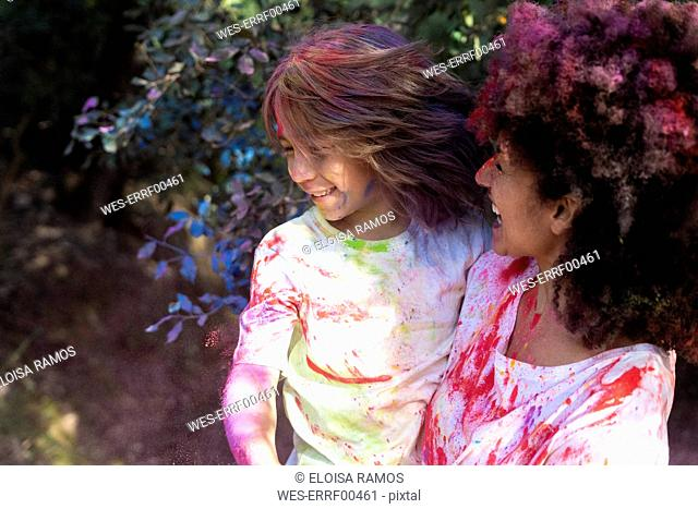 Mother and son full of colorful powder paint, celebrating Holi, Festival of Colors
