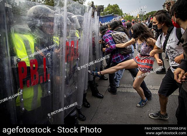 26 September 2020, Mexico, Mexiko-Stadt: Juvenile demonstrators step on a police chain. More than 2500 people take part in a march to commemorate the sixth...