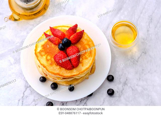 Tasty pancakes with fresh strawberry and blueberry on white plate with teapot on marble background. Table top view