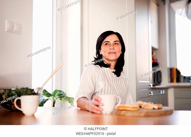 Mature woman sitting at kitchen table, drinking coffee