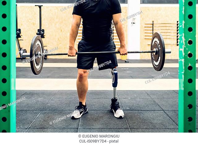 Man with prosthetic leg weight training in gym