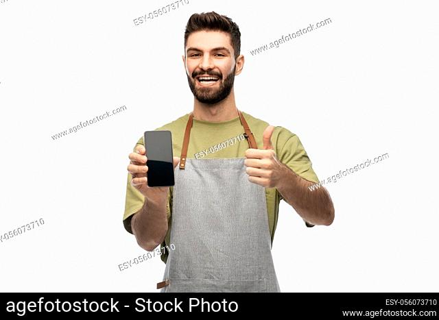 happy barman showing smartphone and thumbs up