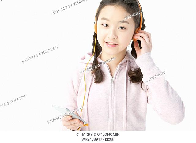 Portrait of smiling school girl listening to music on MP3 player