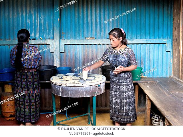 Antigua, Guatemala. Women baking bread and pancakes for shopping and hungry customers walking by her shop inside an indoor market