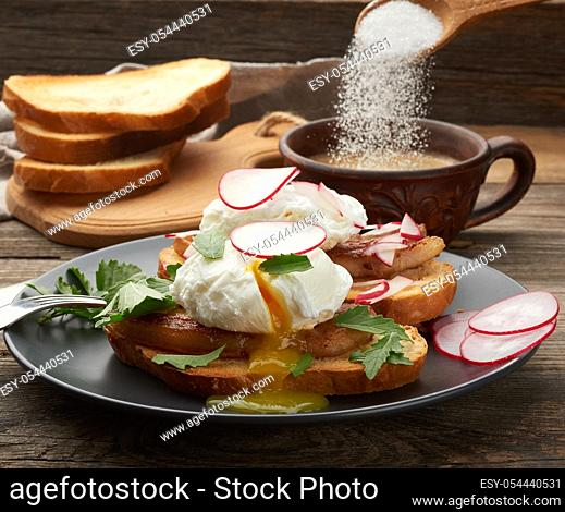 two sandwiches on a toasted white slice of bread with poached eggs, green leaves of arugula and radish in a round plate, behind a cup of coffee