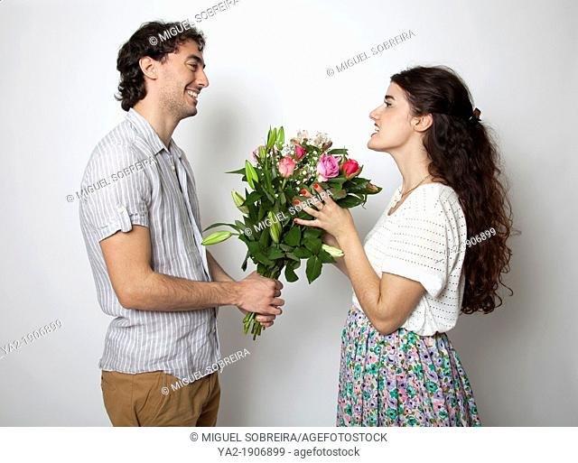 Man handing bouquet of flowers to woman