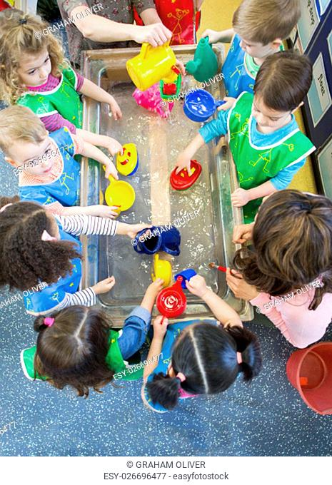 Overhead view of a class of nursery children playing at a water table. They are all wearing aprons and using plastic toys