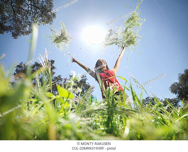 Woman throwing grass in the air