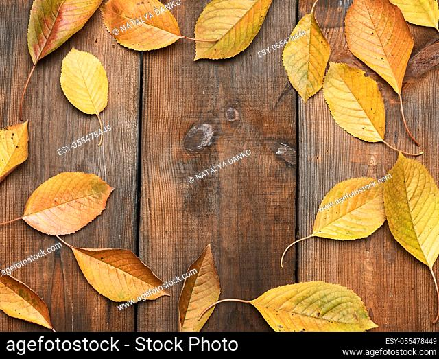 yellow cherry leaves on a brown wooden background, top view, copy space
