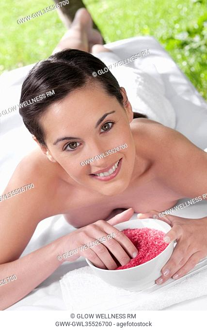Portrait of a woman lying on a massage table and holding a bowl of bath salt