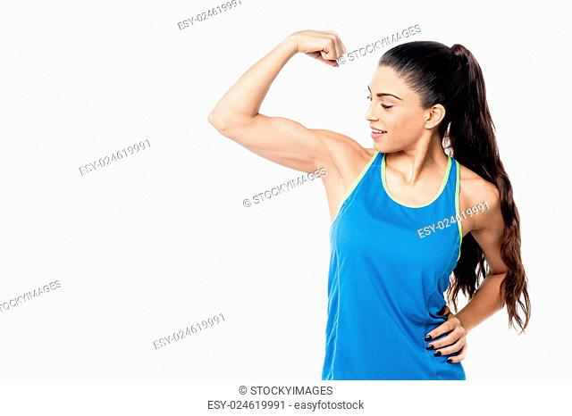 Fitness woman looking at her biceps after exercise