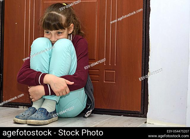 Upset girl sitting at the front door hugging her knees