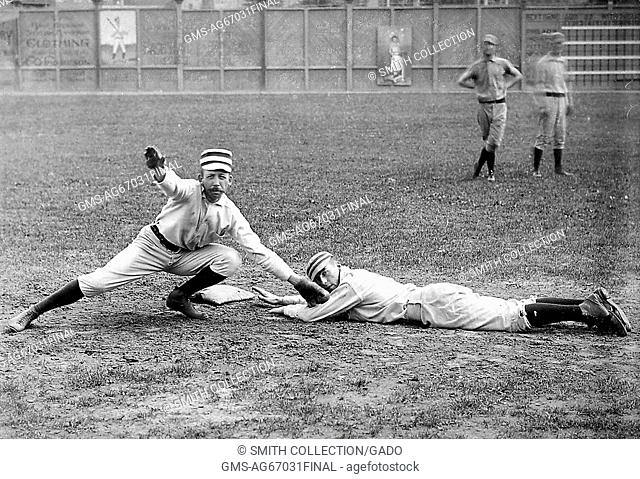 A photographic portrait of two baseball players from the Philadelphia Quakers, Arthur Irwin is pretending to tag out Tommy McCarthy who is pretending to be...