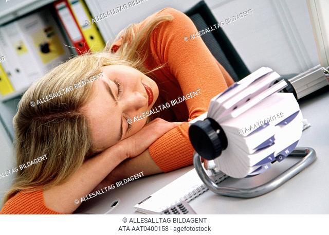 Young woman snoozing at work