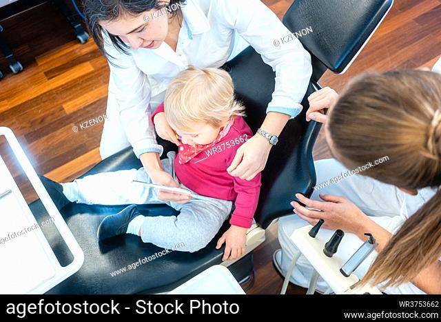 Little child watching with curiosity in mirror being treated by the dentist