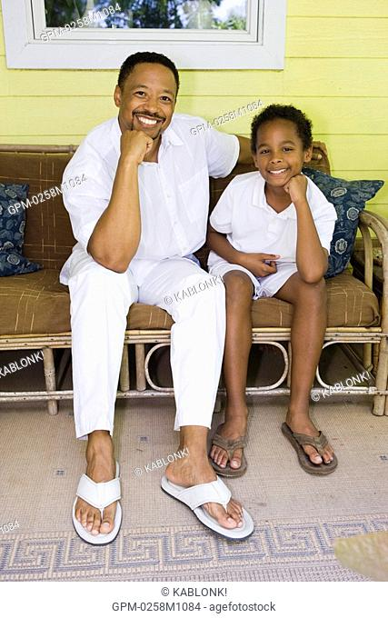Portrait of happy African American father and son sitting outside on porch