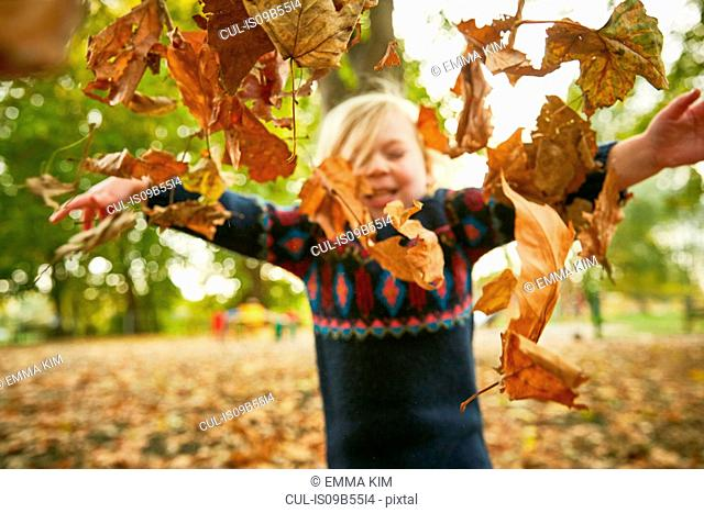 Girl throwing in autumn leaves