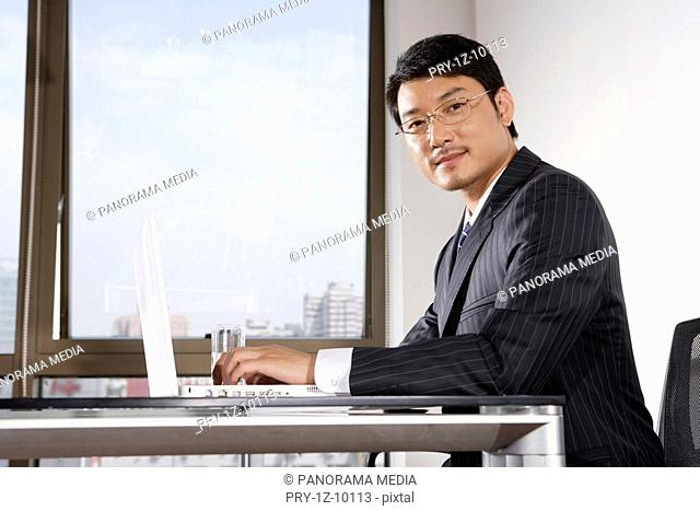 Office man using laptop, sitting on chair, looking at camera