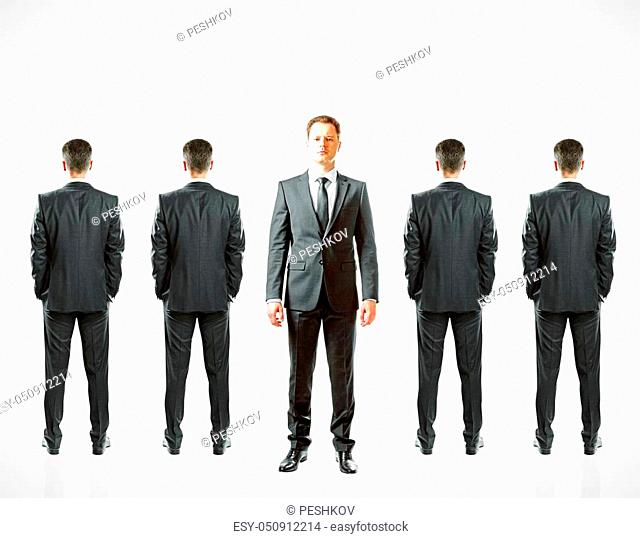 Row of businessmen with only once facing camera. White background. Leadership concept