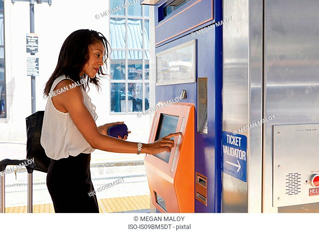 Businesswoman buying train ticket at machine