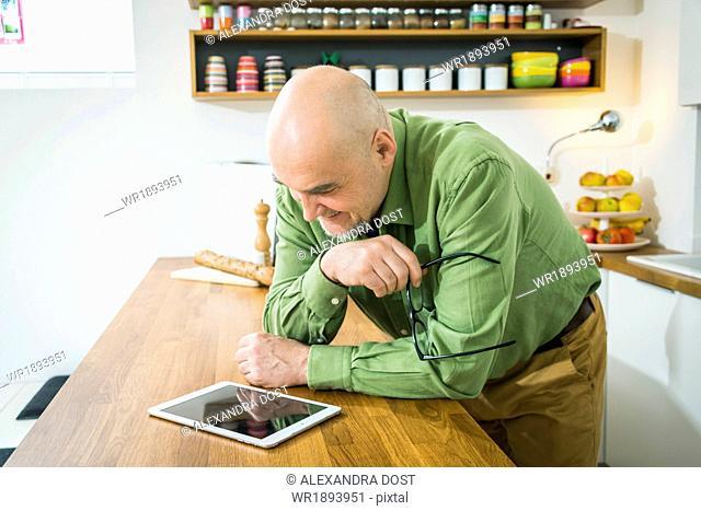 Senior man in kitchen using digital tablet