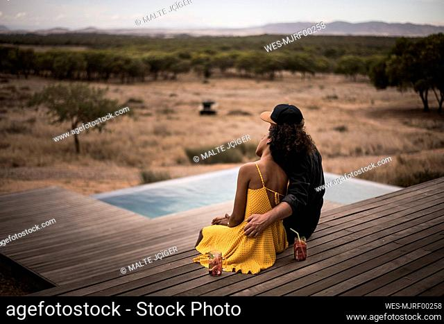 Rear view of couple sitting on deck of a lodge, Cape Town, South Africa