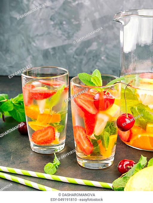 Lemonade with strawberry, mint and ice on a table. Sunny summer day. Copy spase