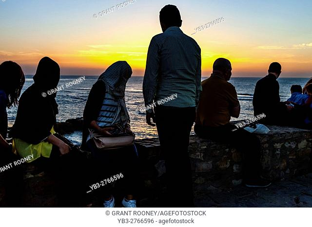 Moroccan People Watch The Sunset From A Popular Viewpoint In The Coastal Resort Of Asilah, Morocco
