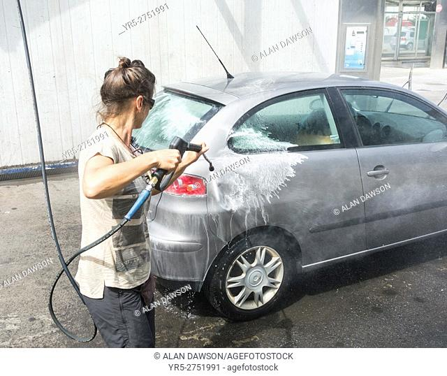 Spanish woman washing car with pressure washer in petrol station in Spain