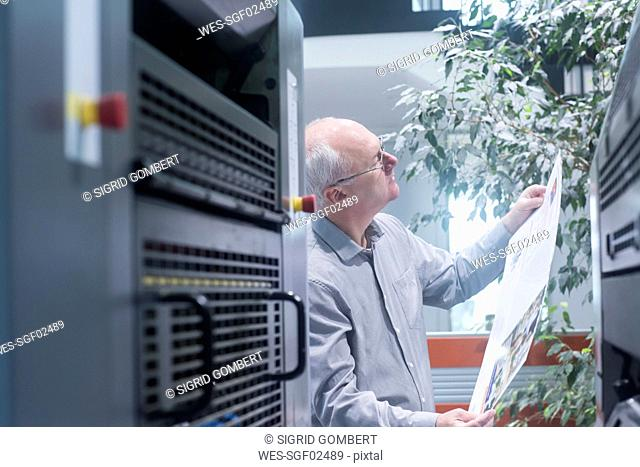 Manager working in printing house, checking paper