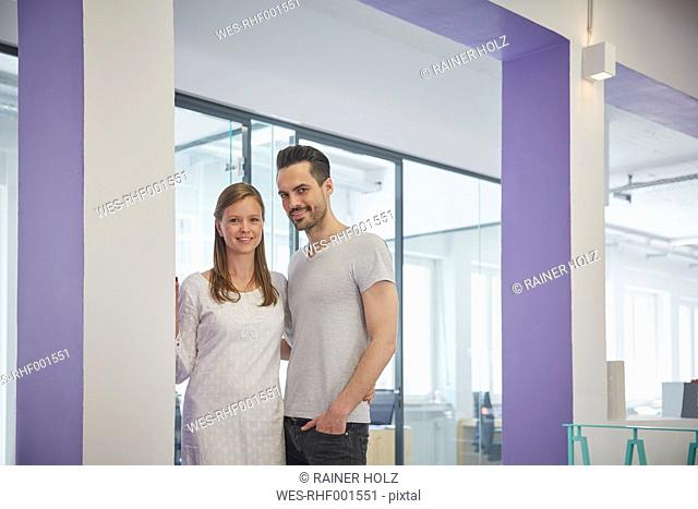 Businessman and woman standing in office with arms around