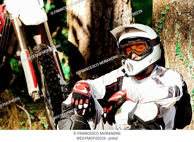 Italy, Motocross biker taking a break in Tuscan forest