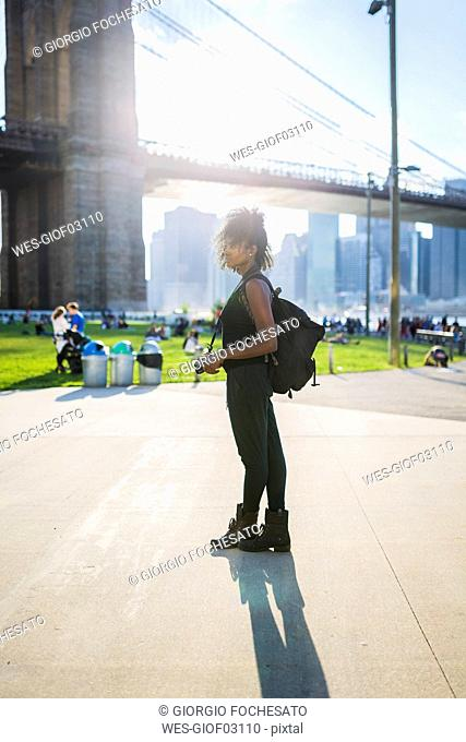 USA, New York City, Brooklyn, woman with camera standing at Brooklyn Bridge