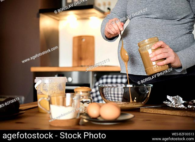 Pregnant woman making healthy cake with tahini, walnuts and dark chocolate at home