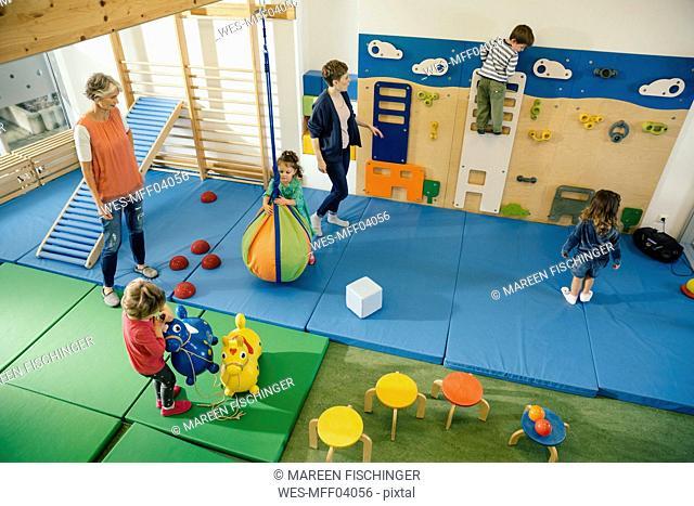 Pre-school teachers and children in gym room in kindergarten