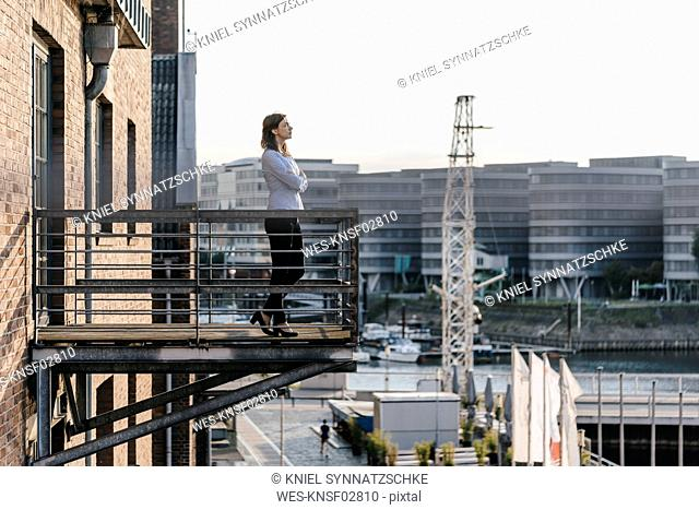 Businesswoman standing on a balcony, with eyes closed