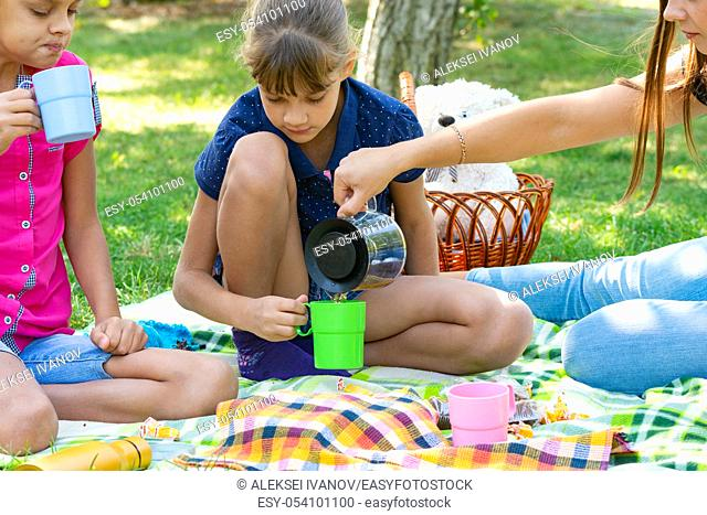 At a picnic, a girl pours tea in glasses for children