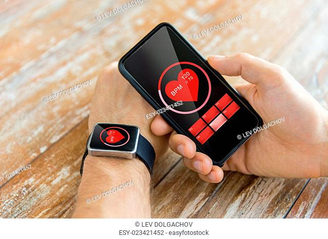business, technology, health care and people concept - close up of male hand holding smart phone and wearing smart watch showing red heart beat icon on screen